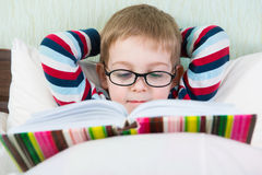 Little cute boy reading book in bed Royalty Free Stock Photography