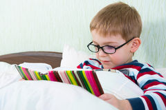 Little cute boy reading book in bed Royalty Free Stock Images