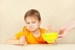 Little cute boy refuses to eat porridge Stock Photo