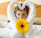 Little cute boy in room after room service. Towel with flower on bed Royalty Free Stock Photo