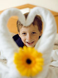 Little cute boy in room after room service. Towel with flower on bed Royalty Free Stock Images