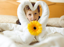 Little cute boy in room after room service. Towel with flower on bed Stock Image