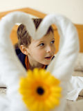 Little cute boy in room after room service. Towel with flower on bed Royalty Free Stock Photography