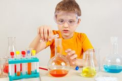 Little cute boy in safety glasses is engaged in chemical experiments in laboratory Stock Photo