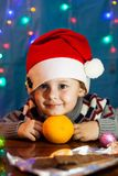 Little cute boy with santa hat. In the background bright festive lights royalty free stock images