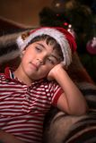 Little cute boy in santa hat is dreaming for a gift Royalty Free Stock Photos