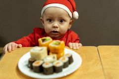 Little cute boy in santa hat looking at a plate of sushi royalty free stock photo