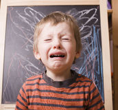 Little cute boy screaming and crying at school. Near blackboard close up Royalty Free Stock Photos