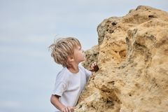 Boy playing with rocks. Little cute boy on sea coast playing with rocks Stock Images