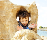 Little cute boy on sea coast thumbs up playing with rocks, lifes. Tyle people concept close up Stock Photography