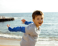Little cute boy on sea coast thumbs up playing with rocks. Little cute real boy on sea coast thumbs up playing with rocks Royalty Free Stock Images