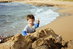 Little cute boy on sea coast thumbs up playing with rocks Royalty Free Stock Photography