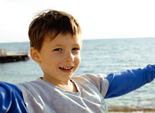 Little cute boy on sea coast thumbs up playing with rocks Stock Photo