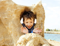 Little cute boy on sea coast thumbs up playing with rocks Stock Image