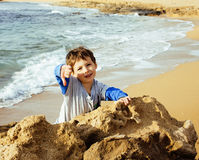 Little cute boy on sea coast thumbs up playing with rocks. Little cute real boy on sea coast thumbs up playing with rocks Royalty Free Stock Image