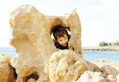 Little cute boy on sea coast thumbs up playing with rocks Royalty Free Stock Photo