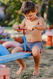 Little cute boy without shirt playing on the Playground, riding a wooden swing. In the summer Royalty Free Stock Images