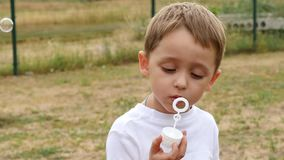 A little cute boy sits on a bench in the park and slowly inflates soap bubbles. The face of the child close up. stock footage