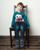 Little cute  boy is sitting on the chair Royalty Free Stock Photography