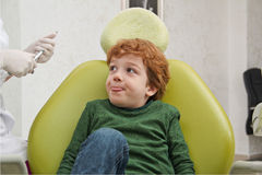 Little cute boy sitting in chair at dentist Stock Image