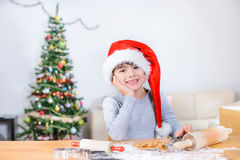 Little cute boy sitting in front of the table with ginger cookies leaning on his arm royalty free stock photo