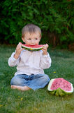 Little cute boy sitting on grass in park and eating a watermelon Stock Image