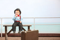 Little cute boy sitting with luggage. Children Travel Concept. Happy boy sitting near a suitcase. He is wearing a hat. The suitcase is old. Isolated on white stock photography