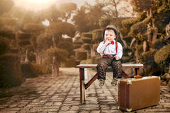 Little cute boy sitting with luggage. Children Travel Concept. Happy boy sitting near a suitcase. He is wearing a hat. The suitcase is old. Isolated on white stock photo