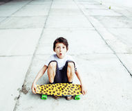 Little cute boy with skateboard on playground alone training, ma Stock Photography
