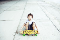 Little cute boy with skateboard on playground alone training, making funy faces Royalty Free Stock Photography