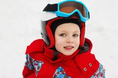 Little cute boy with skis and a ski outfit. Little skier in the Royalty Free Stock Image