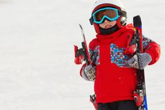 Little cute boy with skis and a ski outfit. Little skier in the Stock Photo
