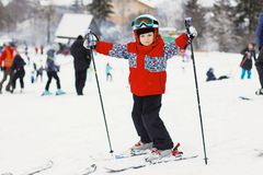 Little cute boy with skis and a ski outfit. Little skier in the Stock Image