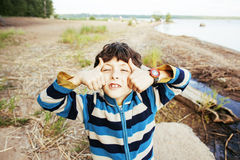 Little cute boy smiling thumbs up on lake shore at summer vacati Stock Image