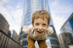 Little cute boy standing near business building, smiling Royalty Free Stock Photo