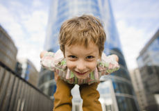 Little cute boy standing near business building, smiling Royalty Free Stock Photography