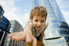 Little cute boy standing near business building, smiling Stock Image