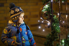 Little cute boy standing outdoors at Christmas time with illumin Royalty Free Stock Images