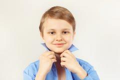 Little cute boy straighten collar of bright shirt Stock Image