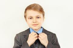 Little cute boy straighten collar of elegant suit Stock Image