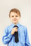 Little cute boy straighten tie over bright shirt Royalty Free Stock Photo