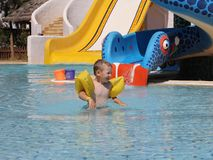 Little cute boy in the summer swims in the pool stock images