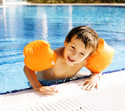 Little cute boy in swimming pool wearing handcarves. Little cute boy in swimming pool wearing orange handcarves royalty free stock photography