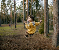 Little cute boy swinging in wood, lifestyle people concept Royalty Free Stock Images