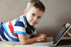 Little cute boy in a green T-shirt playing games on a tablet and watching cartoons. Toddler with tablet. stock photo