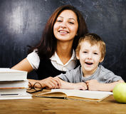Little cute boy with teacher in classroom at desk Royalty Free Stock Photography