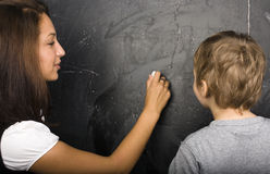 Little cute boy with teacher in classroom Stock Images
