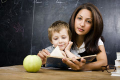 Little cute boy with teacher in classroom, siting at table with books Royalty Free Stock Photos