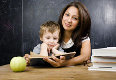 Little cute boy with teacher in classroom, siting at table with books Royalty Free Stock Image
