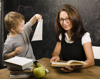 Little cute boy with teacher in classroom Royalty Free Stock Image